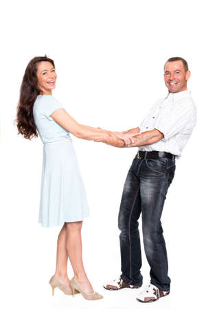 Smiling couple standing in studio in front of white background