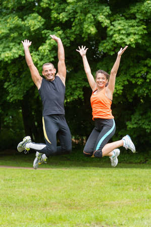 Sport couple in front of green forest photo