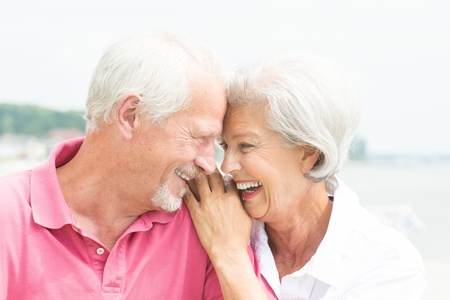 Happy and smiling senior couple at the beach Imagens