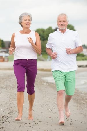 Active and sporty senior couple at the beach Reklamní fotografie - 20600065