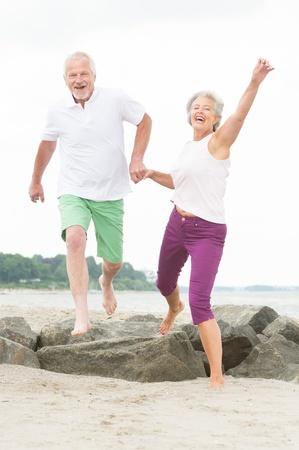 Active and sporty senior couple at the beach Reklamní fotografie - 20600052