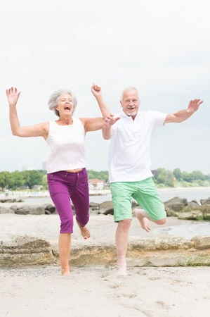Active and sporty senior couple at the beach Reklamní fotografie - 20600076