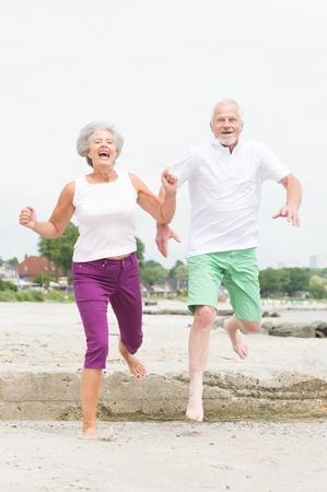 Active and sporty senior couple at the beach Reklamní fotografie - 20600056