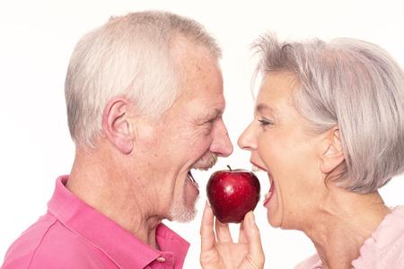Senior paar met appel in de voorkant van de witte achtergrond