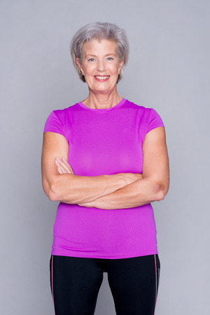 Portrait von sportlichen Senior Frau vor grauem Hintergrund