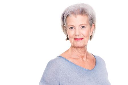 Donna maggiore sorridente di fronte a sfondo bianco