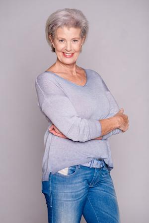 Glückliche ältere Frau vor grauen Hintergrund