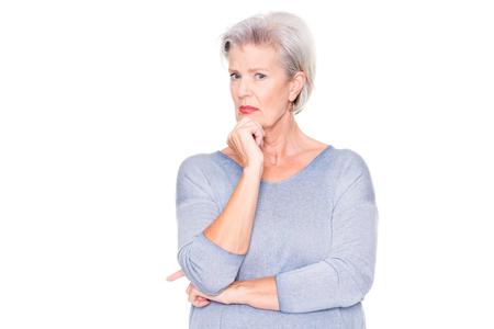 Ältere Frau ist erstaunt über etwas vor weißem Hintergrund