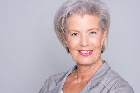 Retrato de una mujer mayor sonriente delante de fondo gris