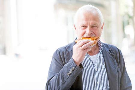 Senior man eats a pizza Imagens - 63161123