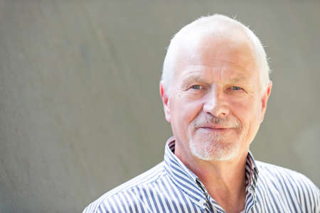 Senior man in front of a grey wall Reklamní fotografie
