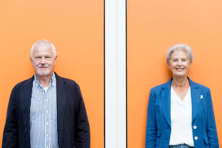 Happy senior couple in front of orange background Reklamní fotografie