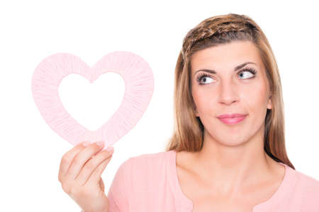 Smiling young woman with pink heart in front of white background