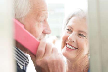 Senior couple call in a phone box Reklamní fotografie