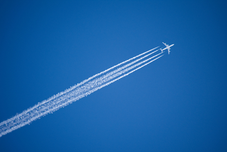 A jet plane flying overhead diagonally leaves four condensation trails against a vivid, blue sky. The picture is reflective of transport, aviation, speed, travel, vacation and success. Stock Photo