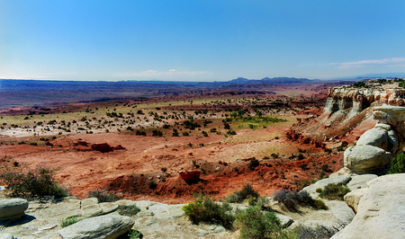 A vista of red and gray rocks with mountains in the background. The picture is colorful with reds and greens across the plains. The picture is reflective of distance, deserts, sky, plains, rock, mountains, heat, and landscape. Taken in San Rafael Salt Was