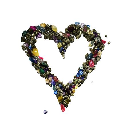 A heart symbol made from bronze colored shiny rocks and gems. The picture is reflective of color, texture, symbols, separated, white