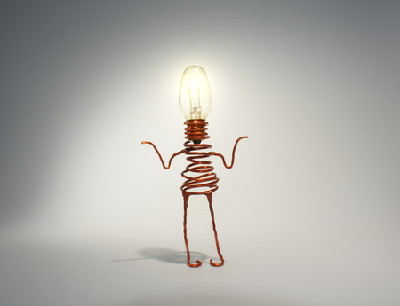 puzzlement: A quirky light globe robot with an illuminated head shrugs. The picture is reflective of quirkiness, not knowing, confusion, friendliness, cuteness, technology, computers, illumination, light, copper, and caricature. Stock Photo