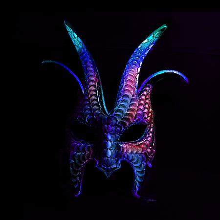 A colorful, scary halloween mask in blues and purples against a black background. Stock Photo