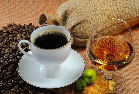 Cup of coffee, cognac glass and bags of coffee beans