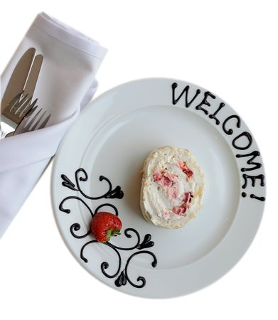 White plate with welcoming chocolate sign and cake  Stock Photo