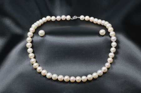 White pearl necklace with pearl earrings on black silk background