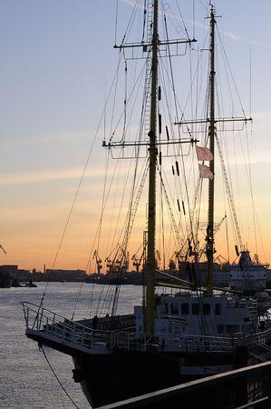 Sailboat moored at a port at sunset