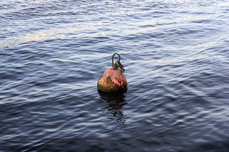 Ancient ship buoy on a river surface