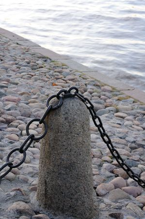 Old fence with a metal chain on the stone embankment of the river