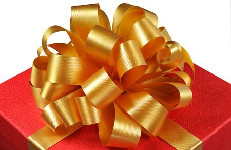 Macro view of red christmas present with a gold ribbon and bow isolated on white