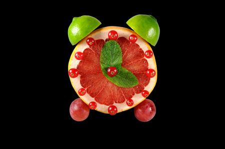 Hand made alarm from fresh fruits isolated on black. Stock Photo