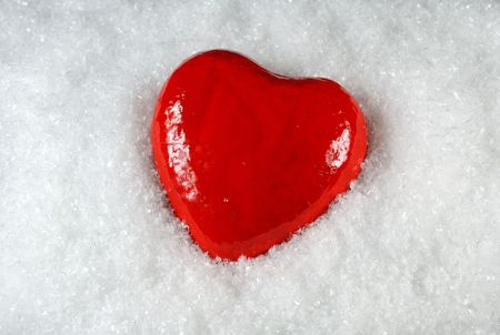 A bright red heart on snow
