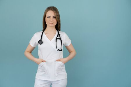 White woman doctor in white clothes looks with a stethoscope on his neck on a blue background Banque d'images