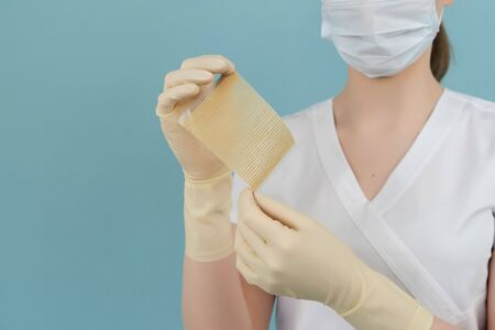 hands holding a burn patch on a blue background