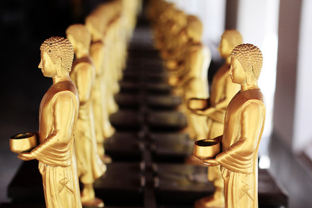 slightly: two rows of small golden buddha images with standing posture holding alms bowls, the back row is slightly crooked Stock Photo