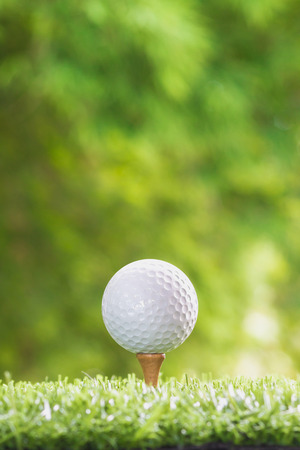 Golf ball on a tee peg and Golf ball on grass. Stock fotó