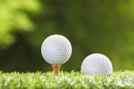 golf  ball: Pelota de golf en un tee clavija y la pelota de golf en hierba.