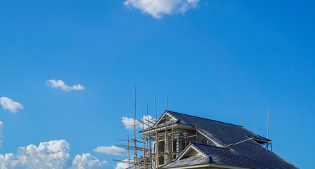 houses with roofing under construction and blue sky