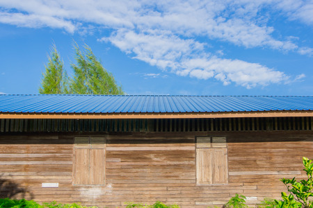 The old wooden building roofed with blue sheet metal roofs and sky background.