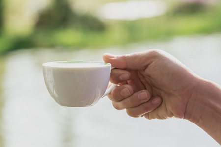 white cup of hot drink in a hand Stock Photo