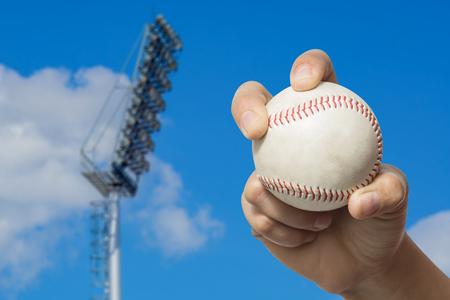 business pitch: Hand holding a baseball on high pole Spotlight Stadium lights with blue sky background.