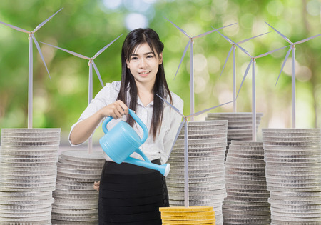 Young businesswoman watering wind turbineon coins with can. concept Wind energy investment