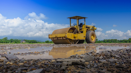 Steamroller compactor soil for adjust level on construction site planting in the field with the help of