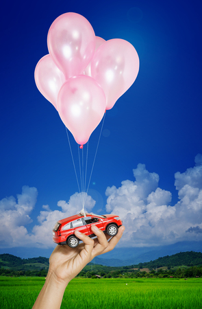red car in hand woman hanging on many balloons flying over blue sky. Automobile asset concept