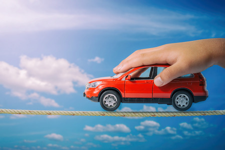 Red car in hand child on rope with blue sky background. Driving safety concept Stock Photo