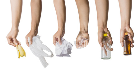 Collections of hand holding banana peel, white plastic bag, crumpled paper, plastic glass and bottles isolated on white background.