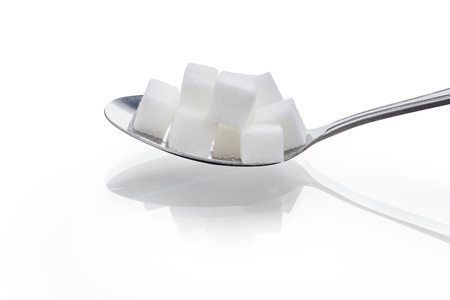 macro close up of cube sugars in spoon isolated on white background.