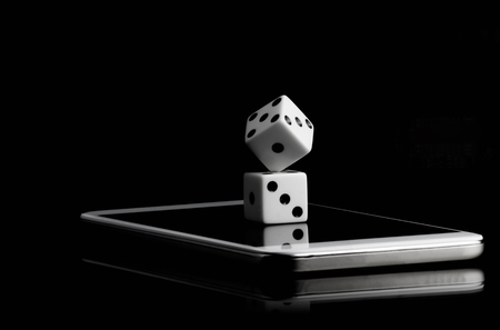 Online risk concept, two white dice stacked on the mobile phone in the black background and copy space for text.