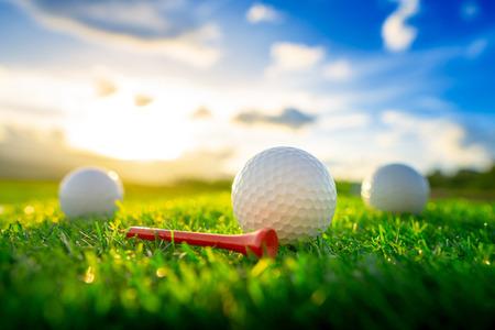 Schließen Sie den Golfball und die roten Abschläge auf dem grünen Hintergrund mit Sonnenuntergang