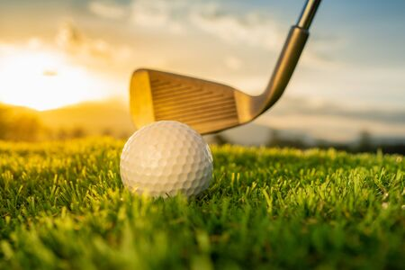 close up iron and golf ball on green grass in golf course at sunset background, sport outdoor